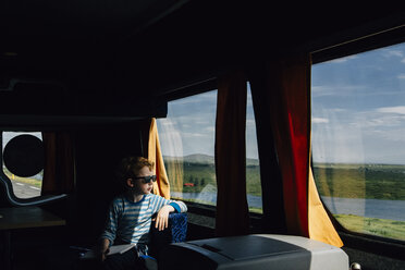 Boy wearing sunglasses looking through window while sitting in motor home - CAVF48791