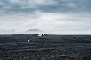 Mid distance view of siblings running towards wrecked airplane on black sand at beach against cloudy sky - CAVF48797
