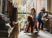 Happy siblings playing at home with dog sitting in foreground - CAVF48803