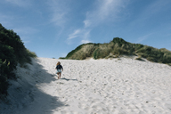 Rear view of girl running on sand at beach during summer - CAVF48806