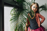 Portrait of girl with messy eyeshadow standing by plants at home - CAVF48809