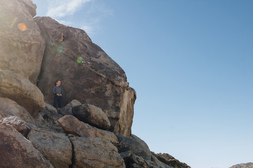 Low angle view of boy standing on rocks against sky during summer - CAVF48815