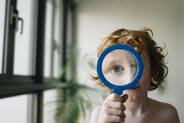 Portrait of shirtless boy playing with magnifying glass at home - CAVF48818