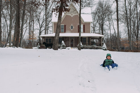 Boy lying on snow covered field against house - CAVF48827