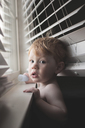 Portrait of shirtless baby boy standing by window at home - CAVF48830