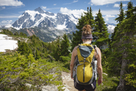 Rear view of female hiker with backpack walking at North Cascades National Park - CAVF48875