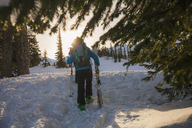 Rear view of male hiker with skies and poles walking in North Cascades National Park during winter - CAVF48878