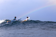 Friends surfing on sea against sky - CAVF48905