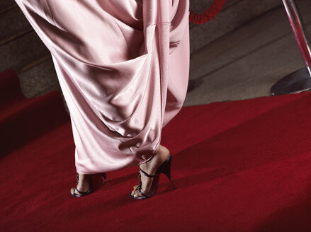 Low section of woman wearing cocktail dress and high heels while walking on red carpet at event - CAVF48932