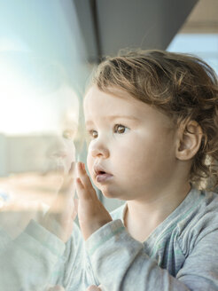 Close-up of cute baby girl looking through window at home - CAVF48938