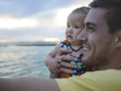 Close-up of father carrying daughter at beach against cloudy sky during sunset - CAVF48941