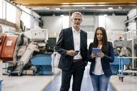 Businessman an woman in high tech enterprise, having a meeting in factory workshop - KNSF04786