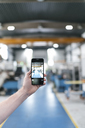 Hand holding smartphone in a factory workshop - KNSF04819