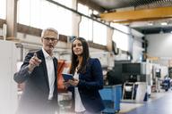 Businessman an woman in high tech enterprise, having a meeting in factory workshop - KNSF04834