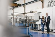 Businessman an woman in high tech enterprise, having a meeting in factory workshop - KNSF04837