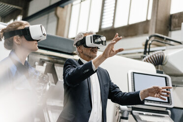 Businessman and skilled worker in high tech enterprise, using VR glasses - KNSF04855