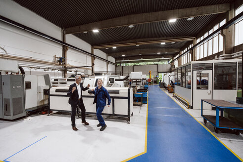 Manager and skilled worker dancing in factory workshop, having fun - KNSF04858