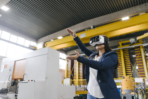 Young woman working in distribution warehouse, wearing VR glasses - KNSF04885