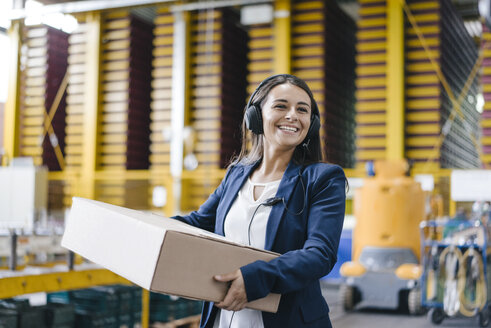Young woman working at parcel service, carrying parcel in warehouse - KNSF04888