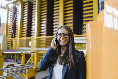 Young woman working in distribution warehouse, talking on the phone - KNSF04894