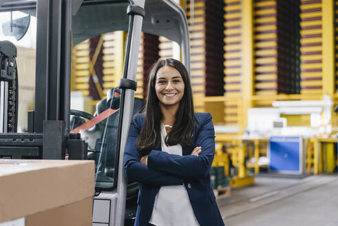 Confident woman standing in logistics center, with arms crossed - KNSF04897