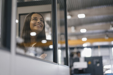 Confident woman working in high tech enterprise, looking out of control room - KNSF04900