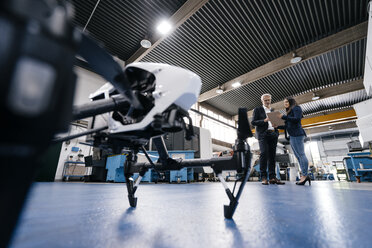 Businessman and coworker discussing production of drones - KNSF04906
