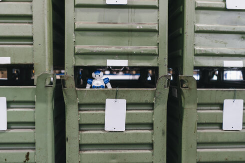 Toy robot looking out of locker in factory storage - KNSF04921