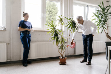 Manager watering plants in recreation room, while worker is drinking coffee - KNSF04930