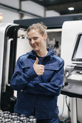 Young woman working as a skilled worker in a high tech company, giving thumbs up - KNSF04939