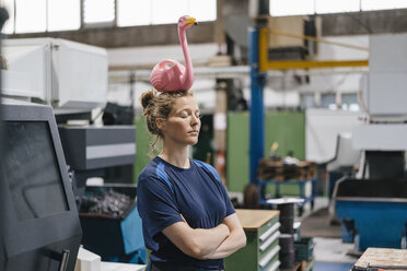 Young woman working as a skilled worker in a high tech company, balancing a pink flamingo on her head - KNSF04954