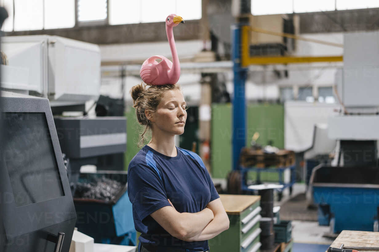 Young woman working as a skilled worker in a high tech company, balancing a pink flamingo on her head - KNSF04954 - Kniel Synnatzschke/Westend61