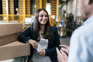 Young woman working in distribution warehouse, talking to colleague - KNSF04963