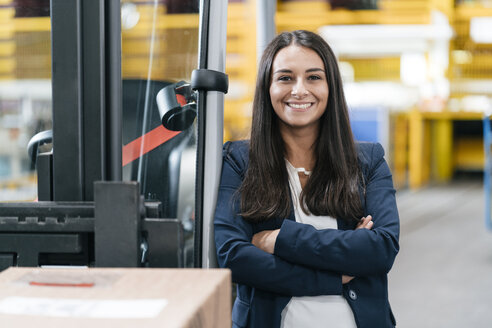 Confident woman standing in logistics center, with arms crossed - KNSF04966