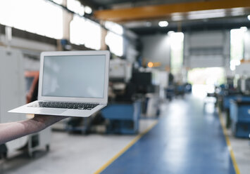 Hand holding laptop with blank screen in a factory workshop - KNSF04975