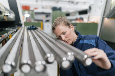 Young woman working as a skilled worker in a high tech company, checking steel rods - KNSF04981