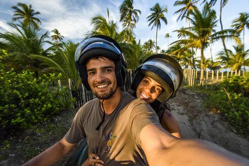 Selfie of couple riding four-wheeler in Taipu de Fora beach, South Bahia near Barra Grande, Brazil - AURF06381