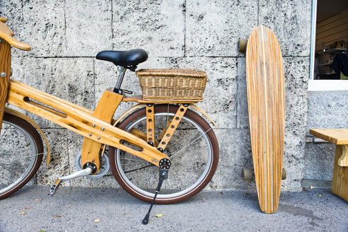 Wooden bike and skateboard leaning against wall, Bled, Upper Carniola, Slovenia - AURF06511