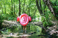 Woman walking in river, carrying an inflatable flamingo - KIJF02018