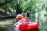 Woman floating on water on an inflatable flamingo - KIJF02021