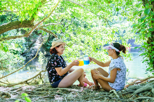 Friends toasting with colorful drinks in glass jars - KIJF02024