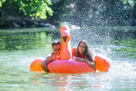 Couple floating on water on an inflatable flamingo - KIJF02027