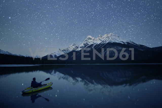 Person kayaking on lake at night, Kananaskis Country, Alberta, Canada - AURF06726 - Cavan Images/Westend61