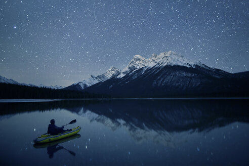 Person kayaking on lake at night, Kananaskis Country, Alberta, Canada - AURF06726