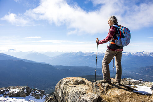 Female hiker looking at view of Garibaldi Provincial Park from top of Whistler Mountain, Whistler, British Columbia, Canada - AURF06822