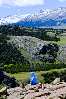 Hiker sitting in scenery with mountains, El Chalten, Santa Cruz Province, Patagonia, Argentina - AURF06924