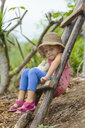 Girl sitting on ladder and looking at camera, Nusa Penida, Bali, Indonesia - AURF07038