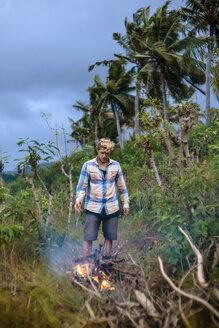 Man near campfire in tropical scenery - AURF07140