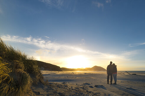 New Zealand, South Island, Puponga, Wharariki Beach, Couple on the beach at sunset - MKFF00431