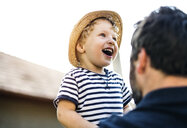 Portrait of laughing toddler on his father's arms - HAPF02733